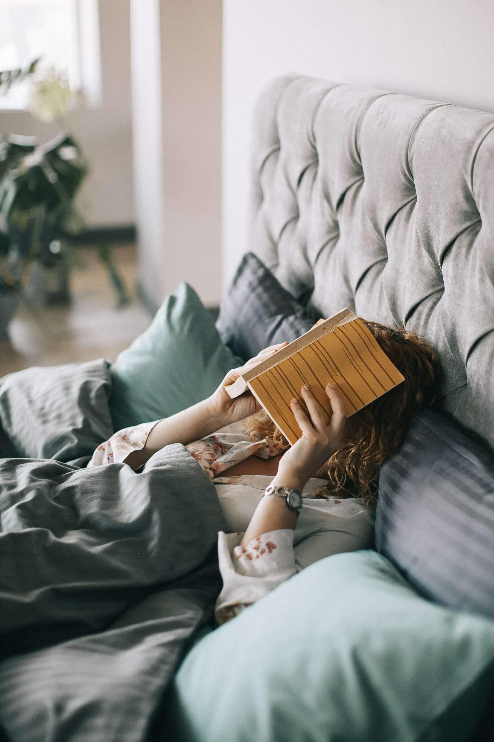 woman covering face with book on bed 1524232 scaled